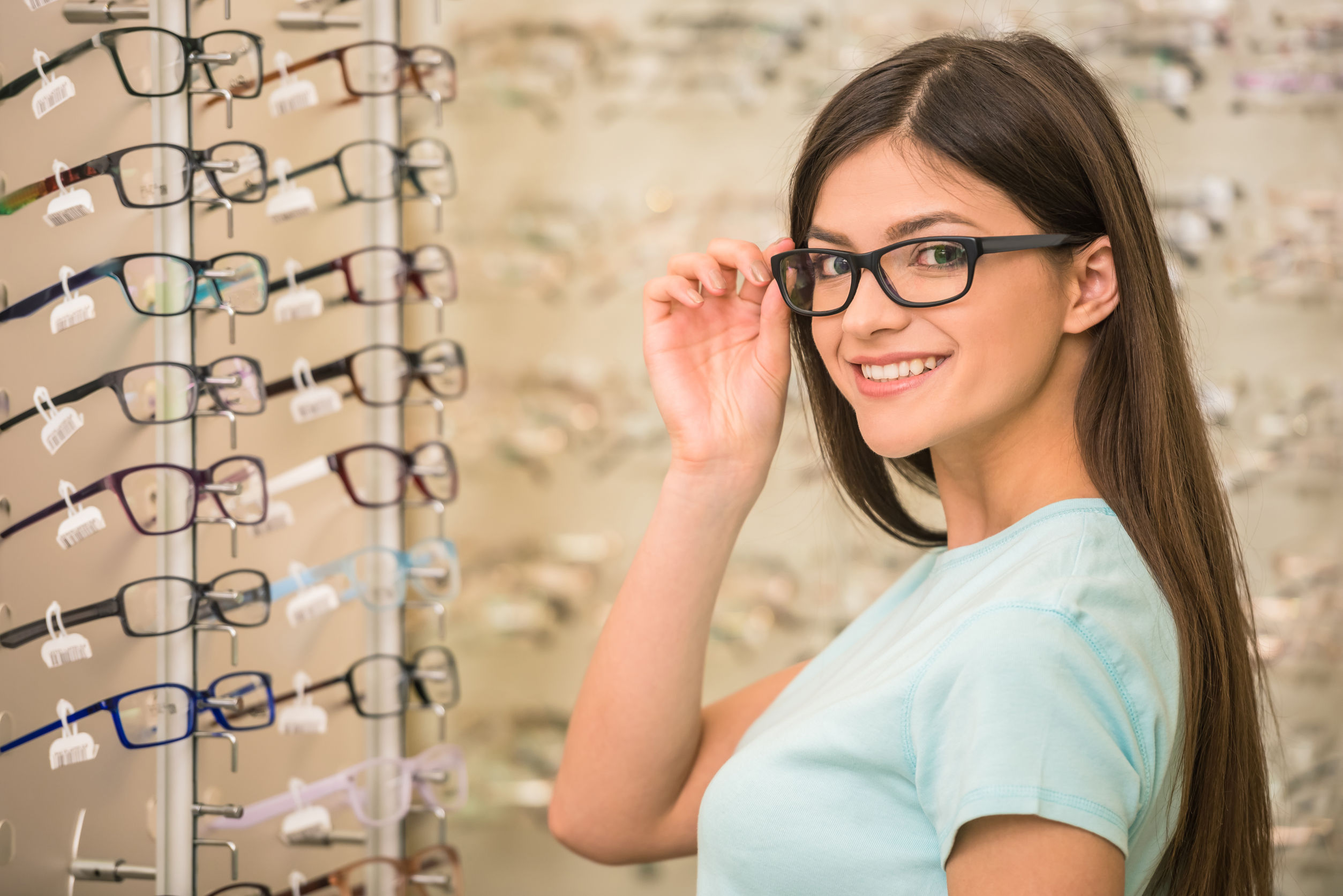 Girl trying on glasses in optical office